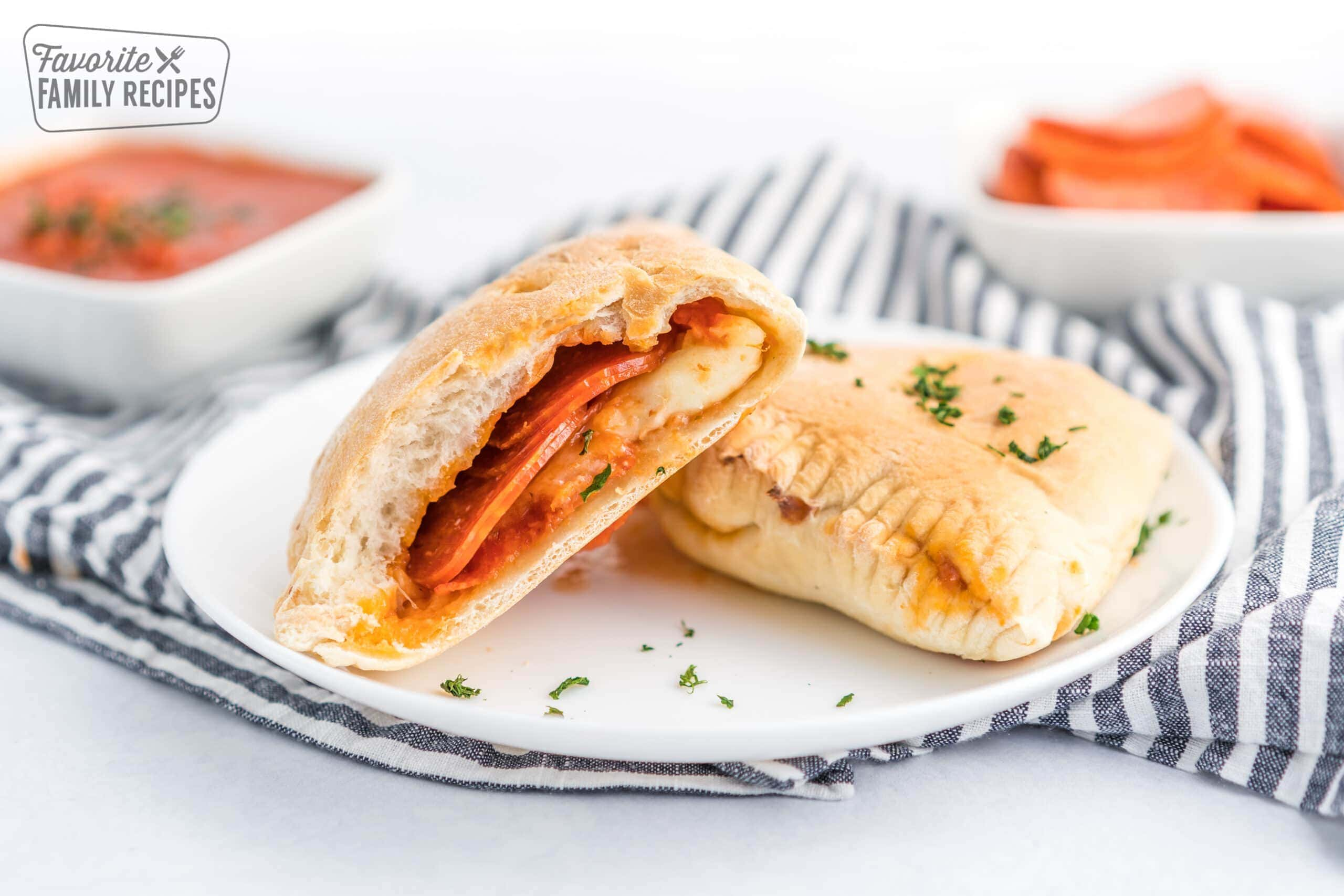A pepperoni calzone cut in half on a white plate