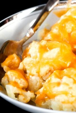 Cheesy Cauliflower Side Dish in a white bowl with a spoon