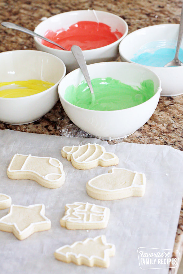 Bowls of red, yellow, green, and blue icing next to cut out sugar cookies