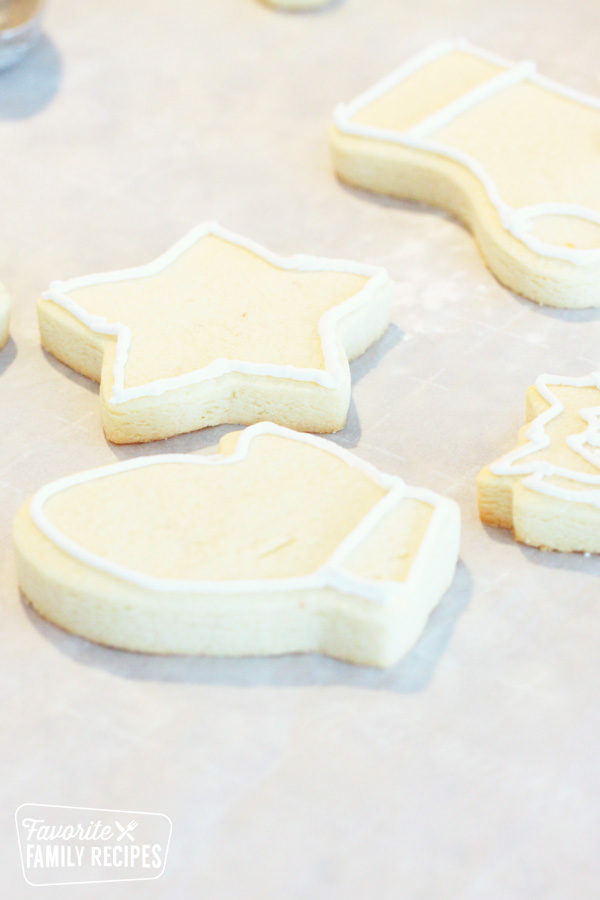 Sugar cookies with royal icing border on parchment paper