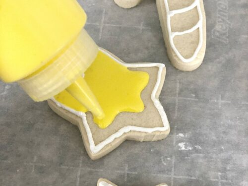 Sugar cookies being decorated with yellow royal flood icing