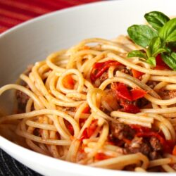 Authentic Italian Spaghetti topped with a garnish in a white bowl.