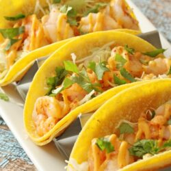 Three shrimp tacos on a plate