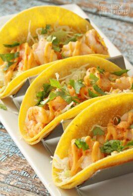 Three shrimp tacos on a plate