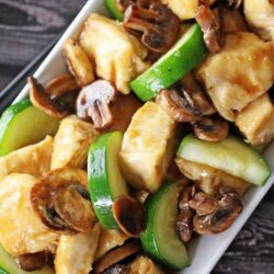 Panda Expres Mushroom Chicken on a plate with chicken, mushrooms, and zucchini