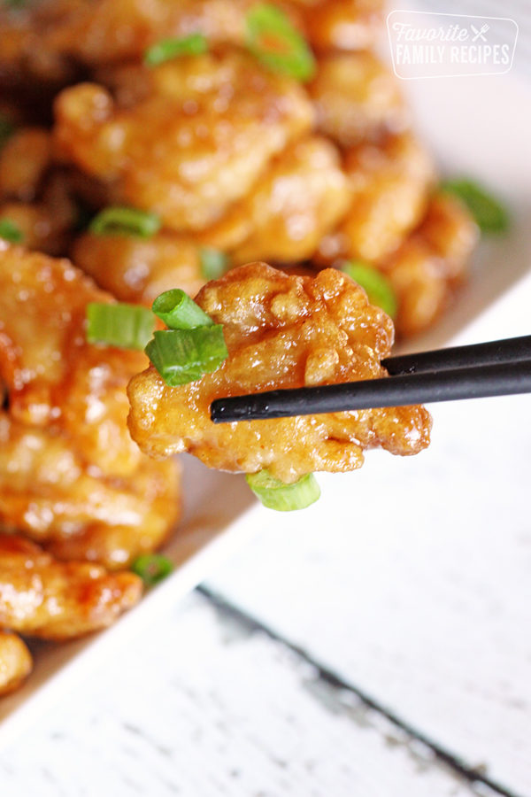 Close up of orange chicken being held with chopsticks