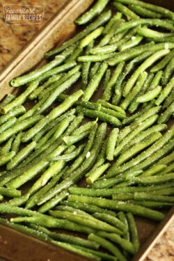 Green beans on a pan ready to be roasted in the oven