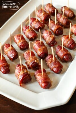 Bacon Wrapped Lil Smokies Appetizer with toothpicks in each one served on a white tray