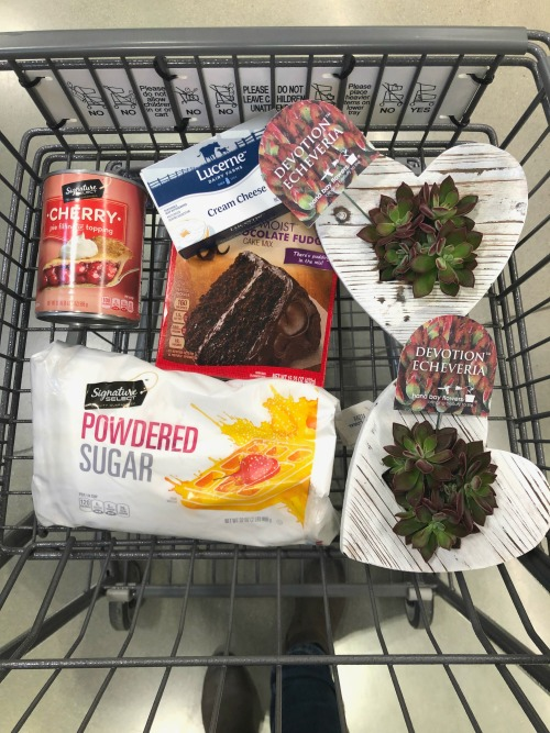 Ingredients to make chocolate cake with cherry topping in a shopping basket