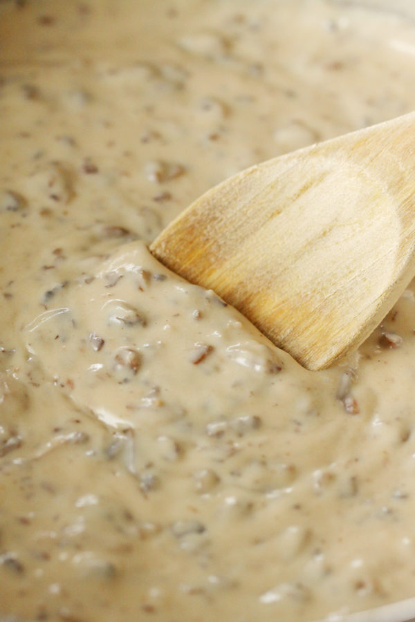 Close up of cream of mushroom soup in a saucepan with wooden spoon