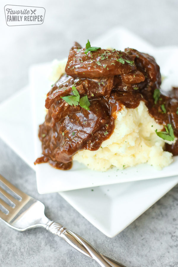 A close-up view of crockpot steak and gravy over mashed potatoes with parsley sprinkled on top