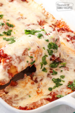 A serving of easy cheesy manicotti being lifted from a pan of manicotti