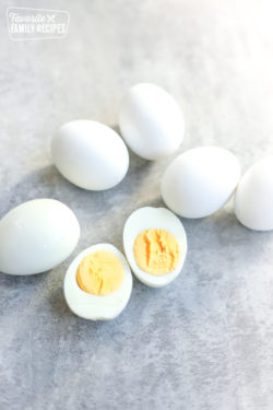 Easy Peel Hard Boiled Eggs on a kitchen counter with one egg peeled and cut in half with the yolk showing.