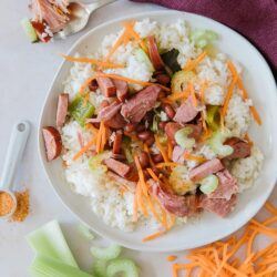 A round white plate of red beans and rice with carrots, celery, ham, and turkey sausage