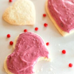 Sugar Cookies with Raspberry Frosting with a bite out of one cookie