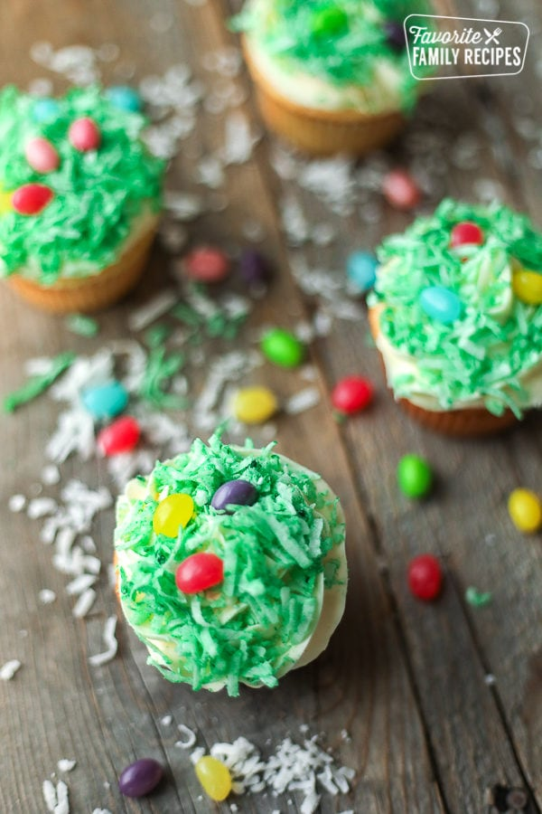 Easter Cupcakes topped with green colored coconut and jelly beans to look like little Easter egg baskets