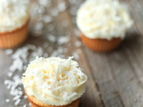 Coconut Cupcakes with coconut frosting on a wooden board with coconut flakes dusting the board