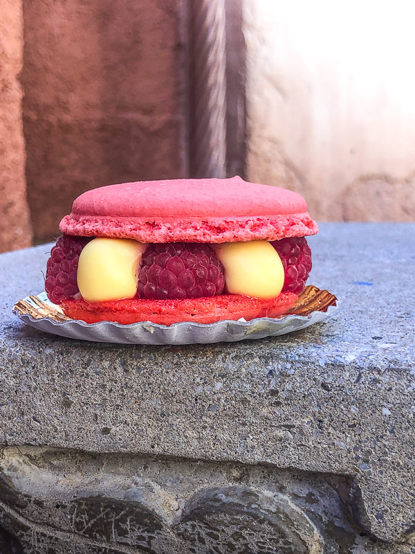 Macaron from Les Halles Boulangerie-Patisserie, a dark pink colored macaroon filled with fresh raspberries and lime cream sitting on a stone bench