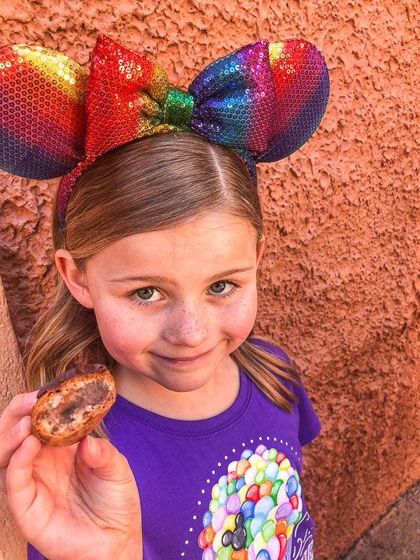A you girl with Minnie Mouse ears holding a chocolate cream parfait from the Les Halles Boulangerie-Patisserie at Epcot Walt Disney World