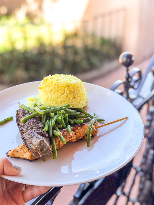 Mix Grill Skewers with marinated beef and chicken served with green beans and rice or roasted potatoes on a plate at Spice Road Table at Epcot's World Showcase