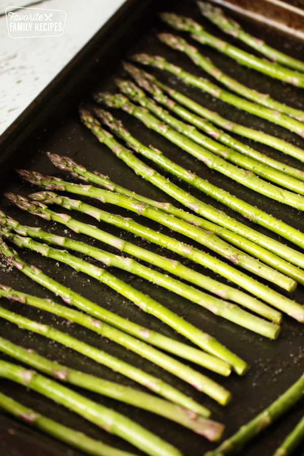 Uncooked asparagus on a baking sheet