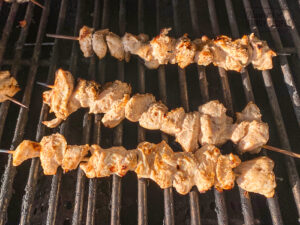 Chicken skewers cooking on grill.