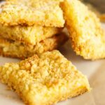 Cream Cheese Lemon Bars stacked on a plate.