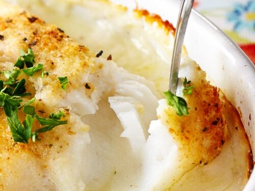Lightly breaded cod in cream sauce being pulled apart with a fork to show flaky texture
