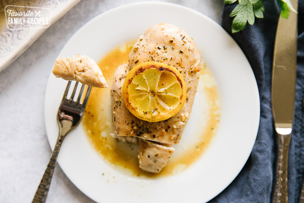 Baked Lemon Chicken topped with a cooked lemon on a plate