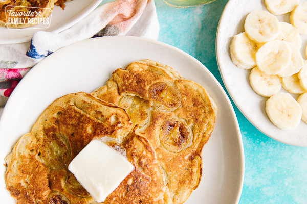Banana pancakes with butter and sliced bananas on the side
