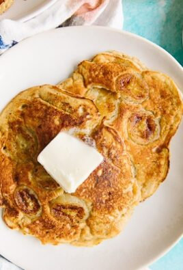 Two banana pancakes on a white plate with butter melting on top