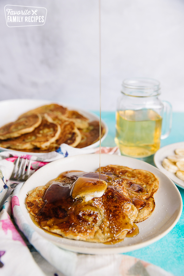 Banana Pancakes with melted butter and syrup being poured over the top