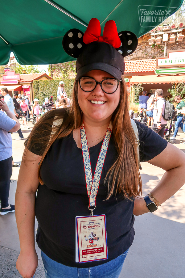Girl wearing a Disney California Adventure Food and Wine Festival Sip and Savor Pass on a Lanyard