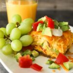 California Breakfast Casserole served on a white plate topped with chopped tomatoes and avocado with green grapes and orange juice on the side