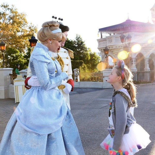 A young girl looking up to Cinderella and Prince Charming at Walt Disney World