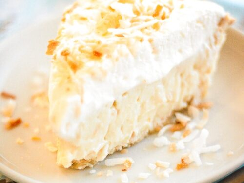 Slice of Coconut Cream Pie on a Plate with toasted coconut