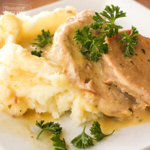 Easy Crock Pot Pork Chops with sauce and mashed potatoes on a white plate.