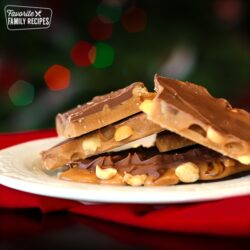 English toffee piled on a white plate with Christmas lights in the background