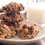 Healthy Oatmeal Cookies stacked on a white plate with a glass of milk in the background.