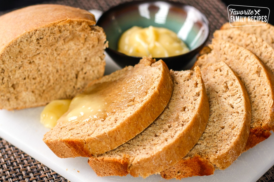 Homemade Honey Wheat Bread Recipe sliced with a side of honey butter.