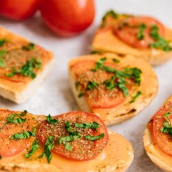 Slices of Cheesy Italian Bread with fresh tomatoes on the side
