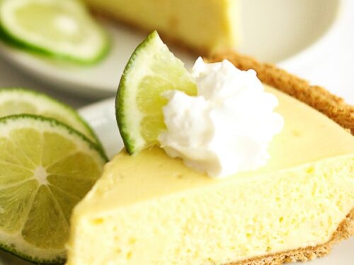 Two slices of Key Lime Pie on separate plates. Each pie is topped with whipped cream and a key lime wedge.