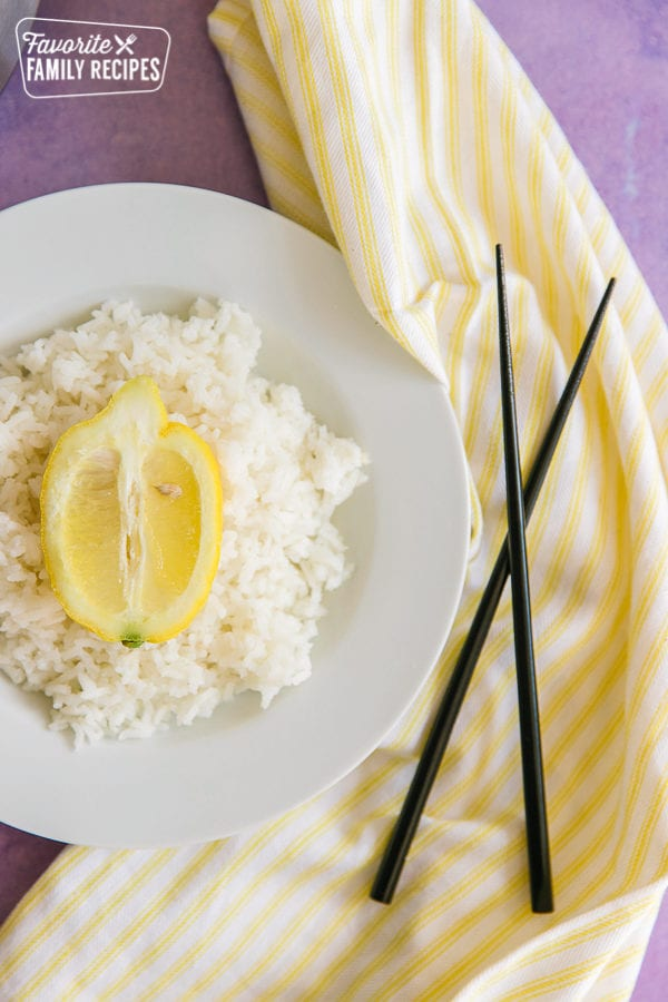 A bowl filled with lemon rice with chopsticks and a yellow napkin to the side