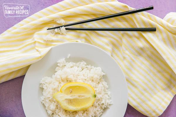 Lemon rice on a plate with chopsticks on the side