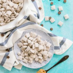 Muddy Buddies on a plate surrounded by chocolate chips and a spoonful of peanut butter.