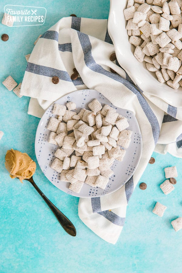 Muddy buddies in a bowl with a blue striped napkin on the side