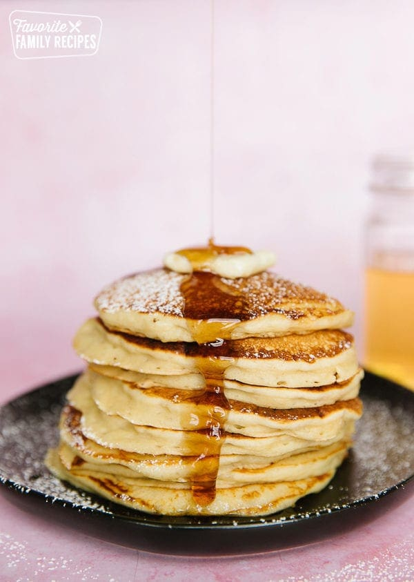 A stack of pancakes from scratch on a black plate with syrup pouring over them