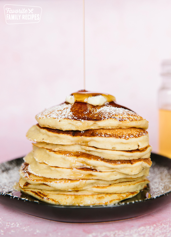 A stack of pancakes with homemade maple syrup being poured over the top.