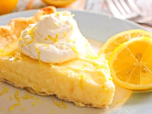 Slice of Sour Cream Lemon Pie on a plate with sliced lemons