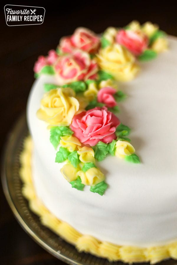 A round cake with white fondant and pink and yellow frosting flowers